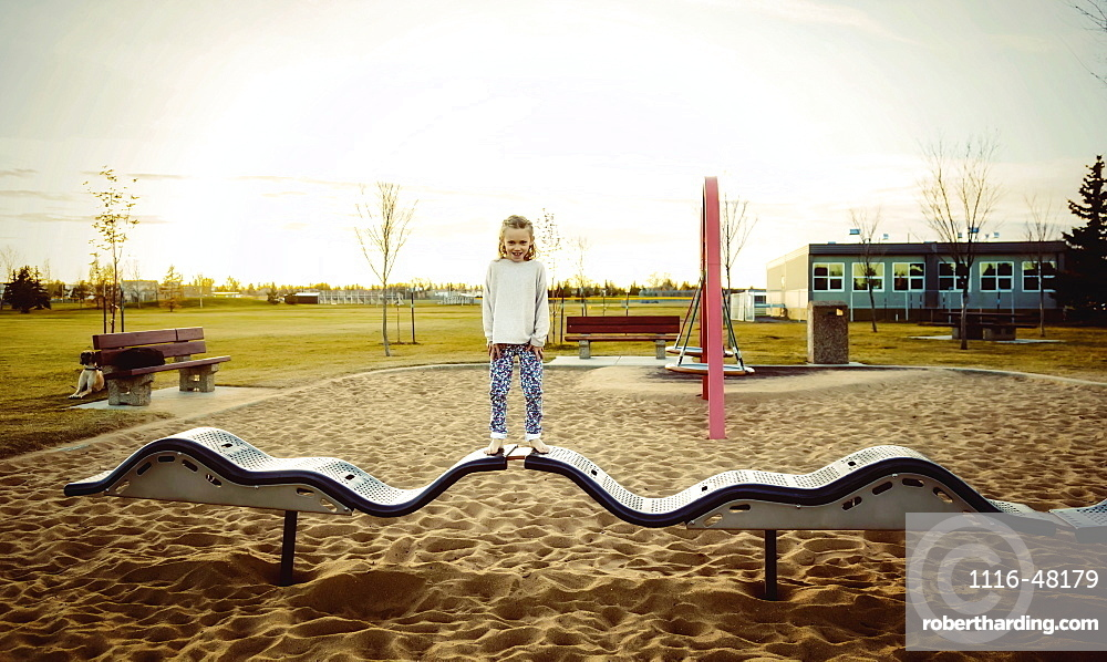 A young girl posing for the camera while standing on a bouncing balance beam in a playground on a warm autumn evening at sunset, Edmonton, Alberta, Canada