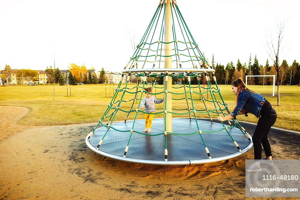A young mom spinning her daughter while playing on a merry go round with a rope climber in a playground at sunset during a warm autumn evening, Edmonton, Alberta, Canada