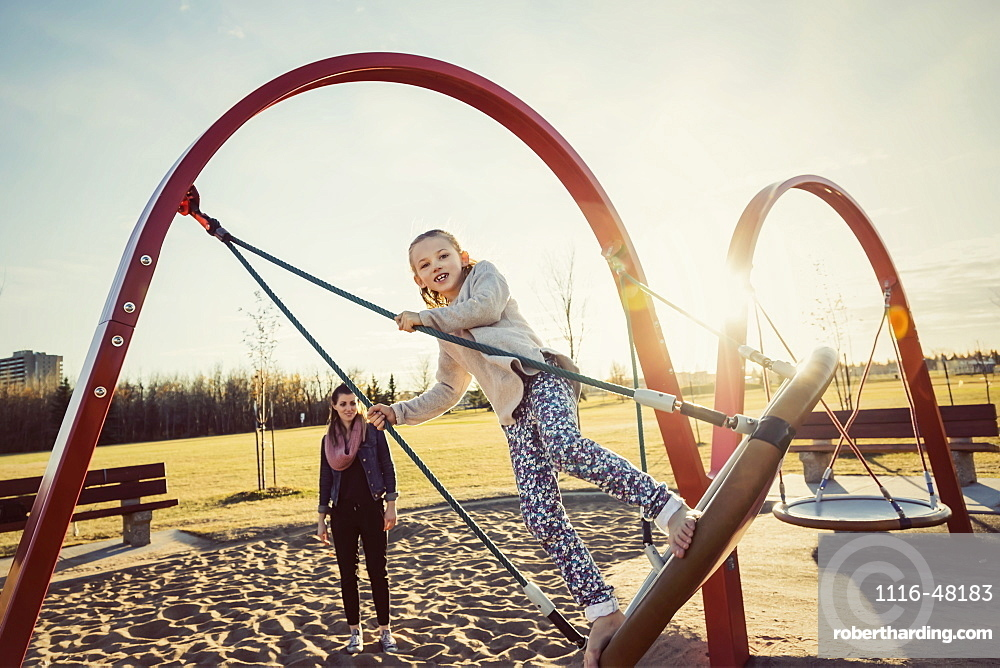 A young mom and her daughter playing on a saucer swing in a playground on a warm autumn evening, Edmonton, Alberta, Canada