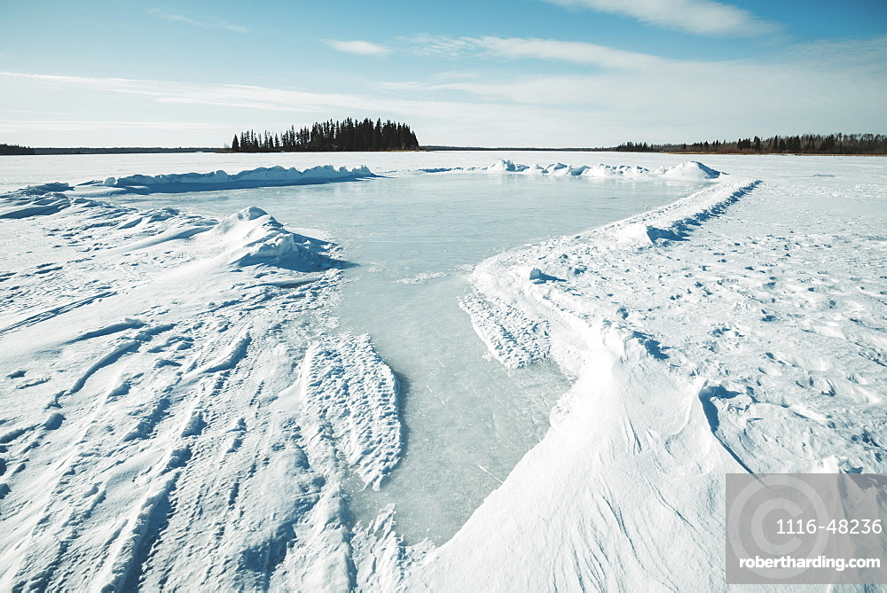Snow drifted and cleared on a frozen lake in Elk Island National Park, Alberta, Canada
