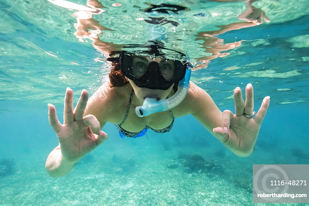 A woman snorkelling and making the 'okay' sign with her hands, Belize Barrier Reef, Belize