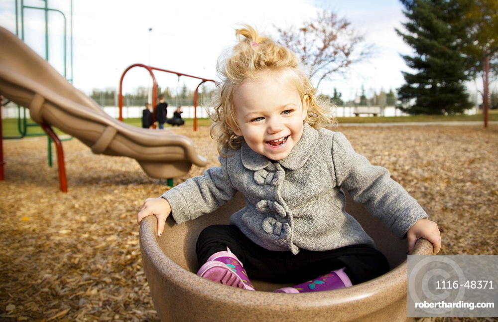 A cute young girl spinning in a saucer on a playground during the fall season, Spruce Grove, Alberta, Canada