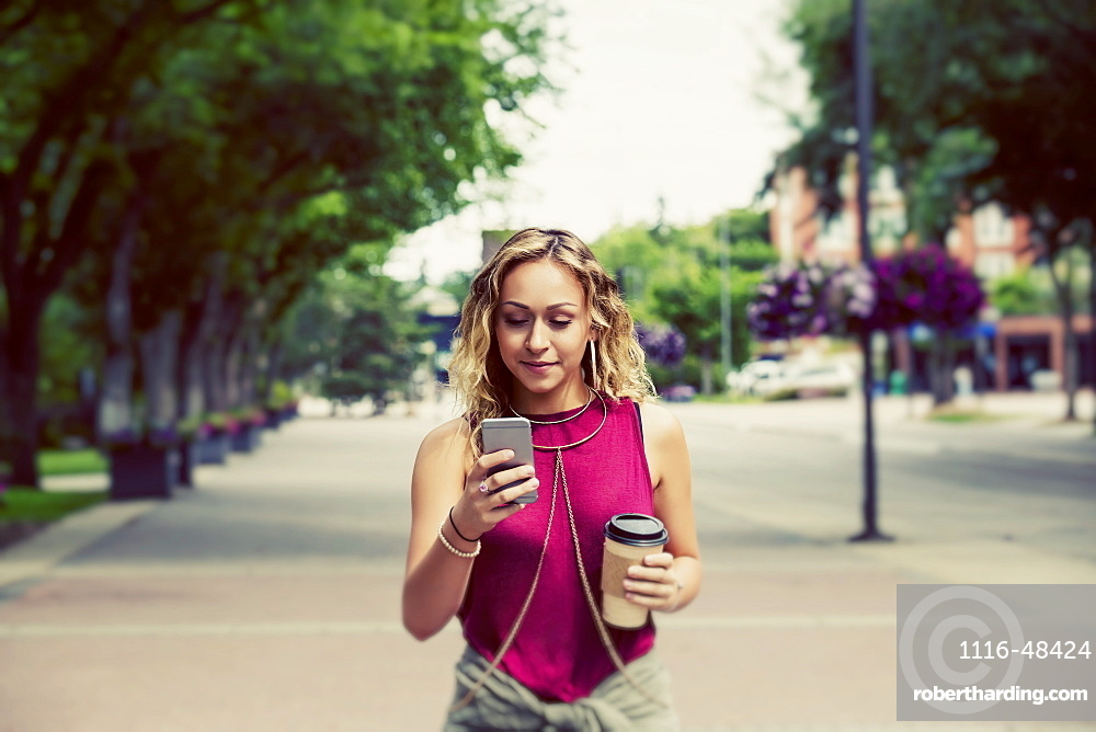 A beautiful young woman walking down a street near a university campus texting on her smart phone, Edmonton, Alberta, Canada