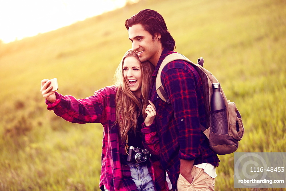 Young couple in a park posing for a self-portrait with their cell phone, Edmonton, Alberta, Canada