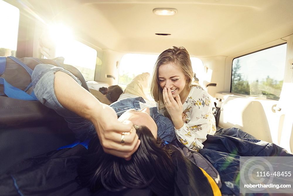 A young couple lays in the back of their vehicle during a road trip talking and laughing together, Edmonton, Alberta, Canada
