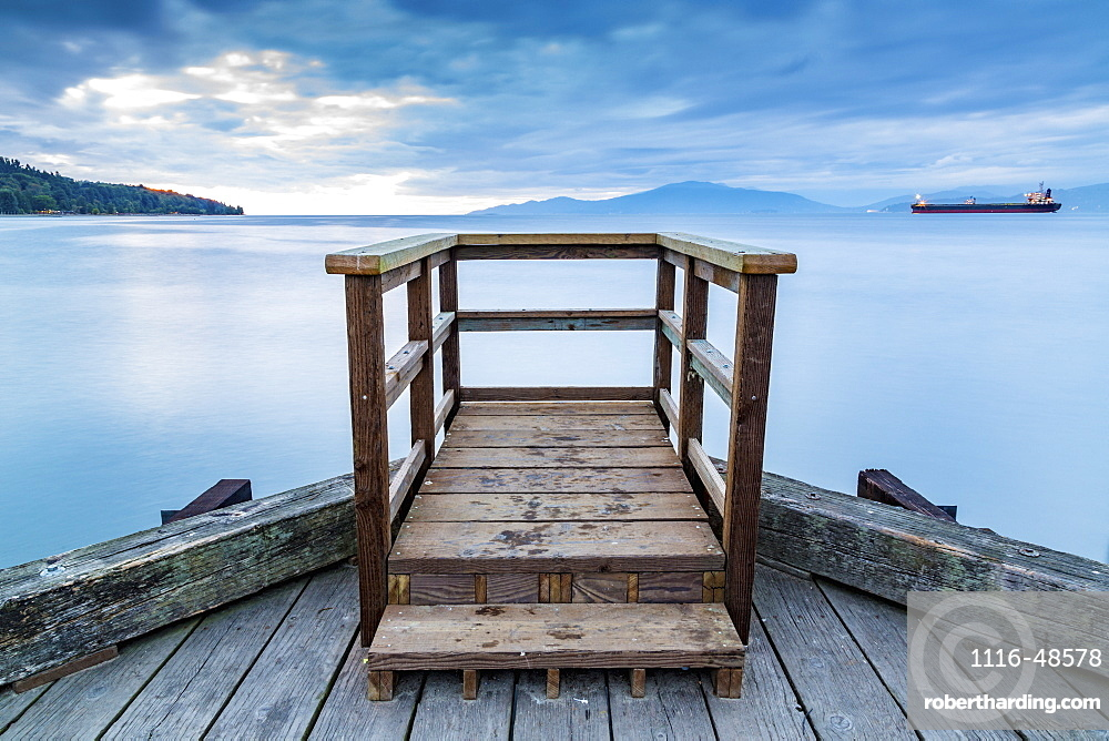 A wooden viewing platform at the end of a dock looks out to a ship on the tranquil ocean, Vancouver, British Columbia, Canada