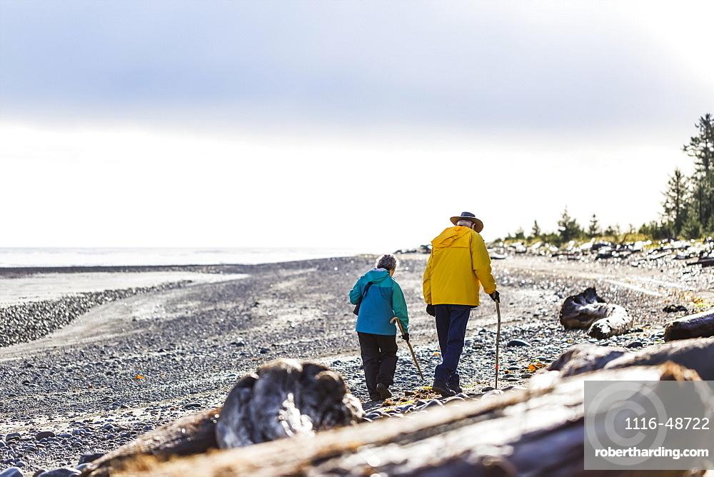 A senior couple hiking with walking sticks on the beach along the coast, Meadow Mist Campground, Graham Island, Tlell, Haida Gwaii, British Columbia, Canada
