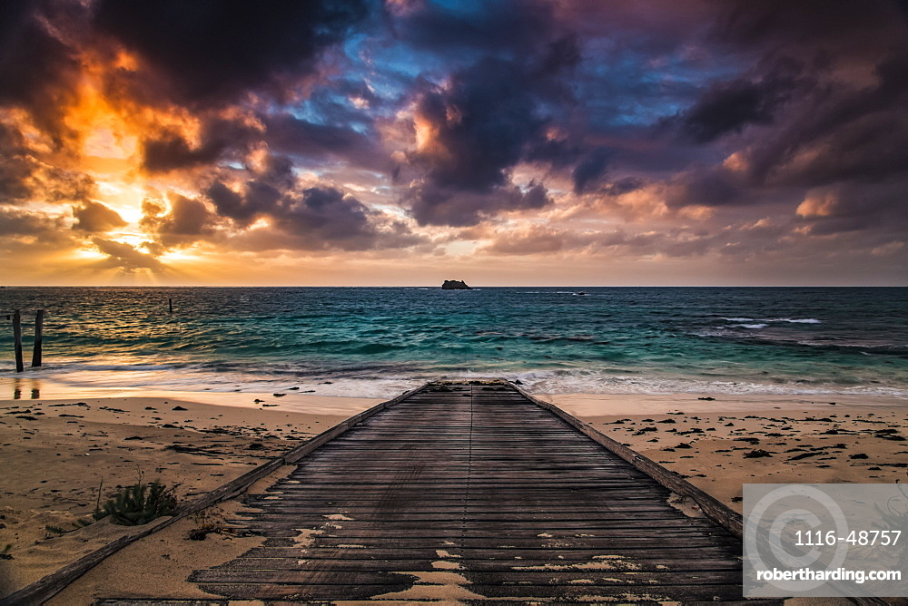 A wooden boardwalk on a beach leading to the turquoise water of Hamelin Bay at sunset, Western Australia, Australia