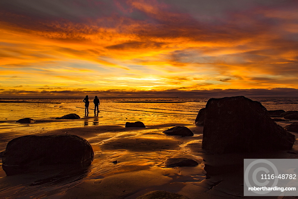 Silhouette of two people standing on Wreck Beach with an orange glow at sunset, Vancouver, British Columbia, Canada