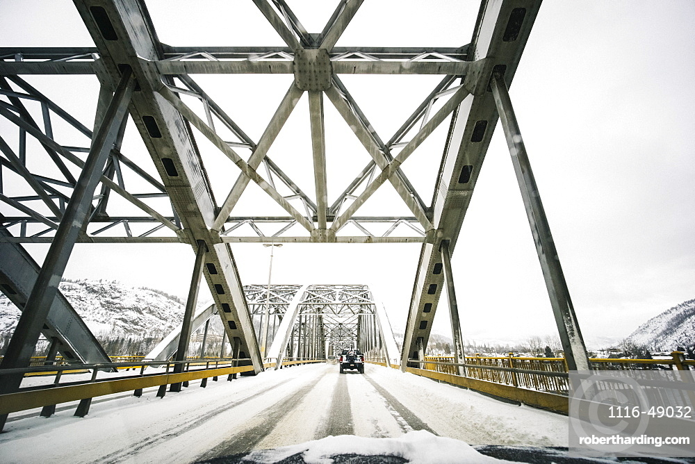 Vehicles traveling on a snow covered road over a bridge with a view from the front of a vehicle, Nelson, British Columbia, Canada