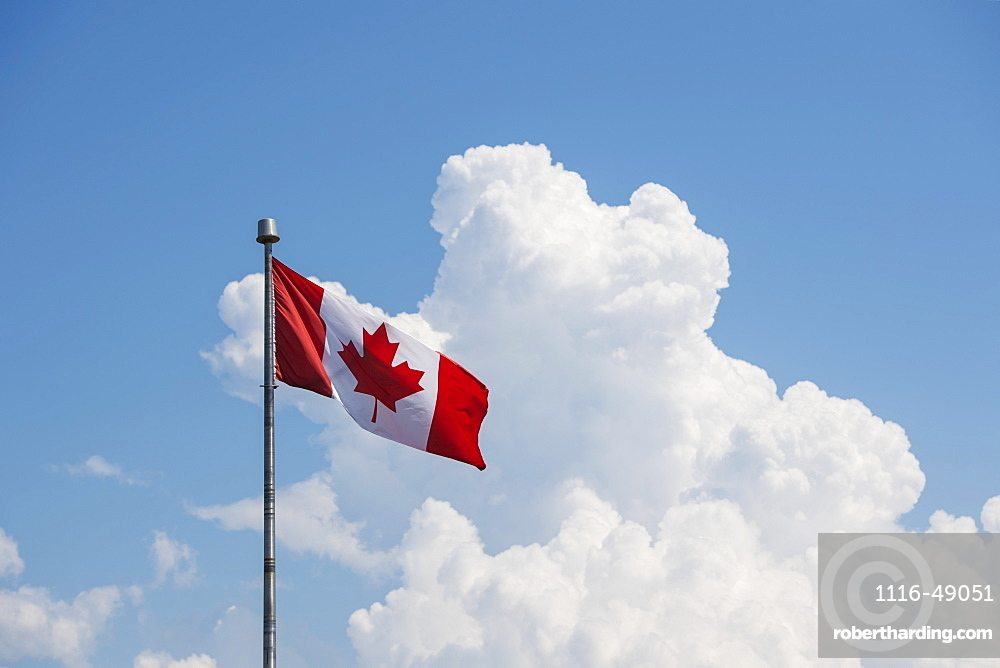 A Canada flag flying in a blue sky with cloud, Prince Edward Island, Canada