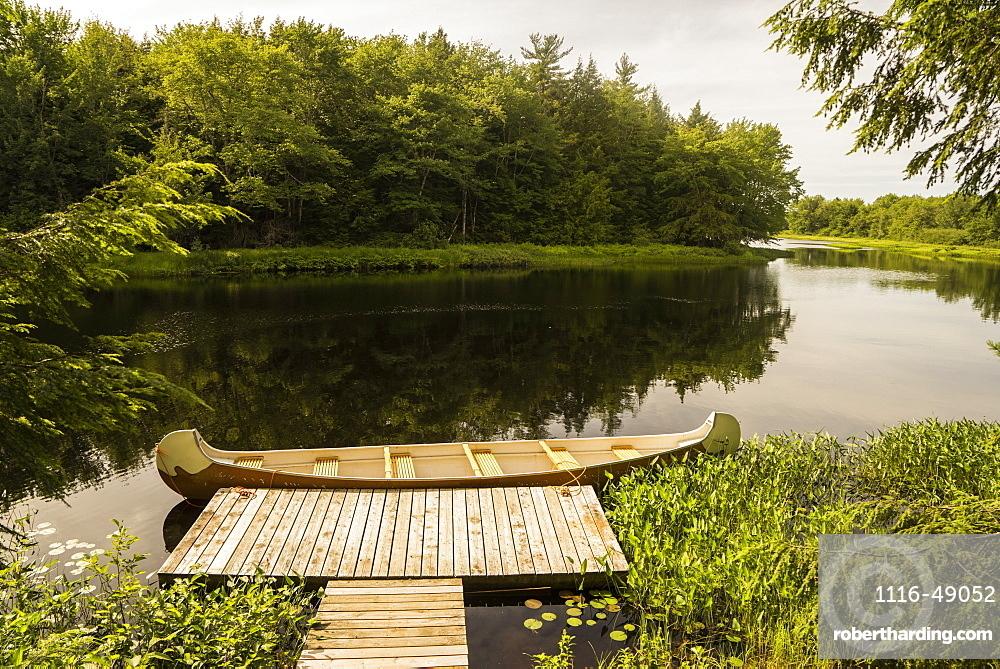 A canoe sitting along a dock in Mersey River, Kejimkujik National Park, Nova Scotia, Canada