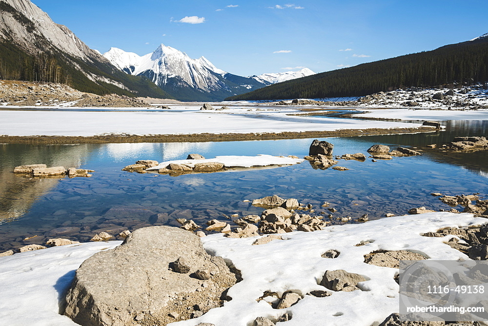 Snow on the lake and snow-capped rugged mountains peaks in Jasper National Park, Alberta, Canada