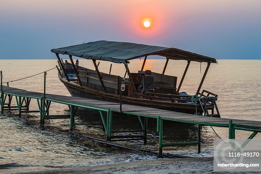 Sun setting behind boat moored to dock at Mbali Mbali Mahale Lodge (Kungue Beach Lodge) on Lake Tanganyika, Tanzania