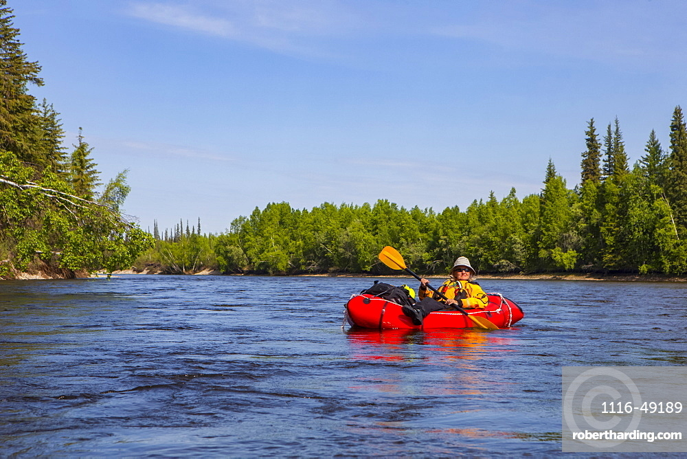 Female packrafter relaxing on a mellow stretch of the Charley River, Yukon–Charley Rivers National Preserve, Alaska, United States of America