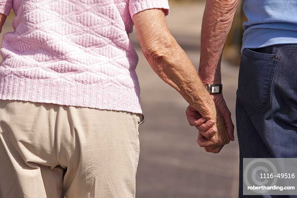 Mid section view of a couple walking with holding hands