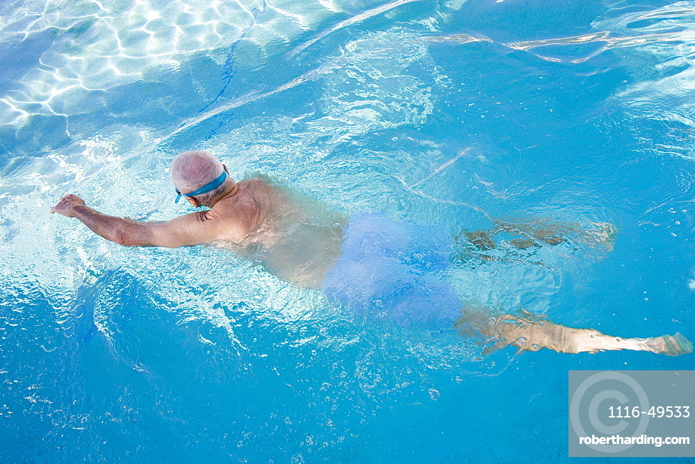 Rear view of a senior man swimming in a swimming pool