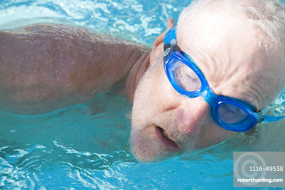 Close-up of a senior man swimming in a swimming pool