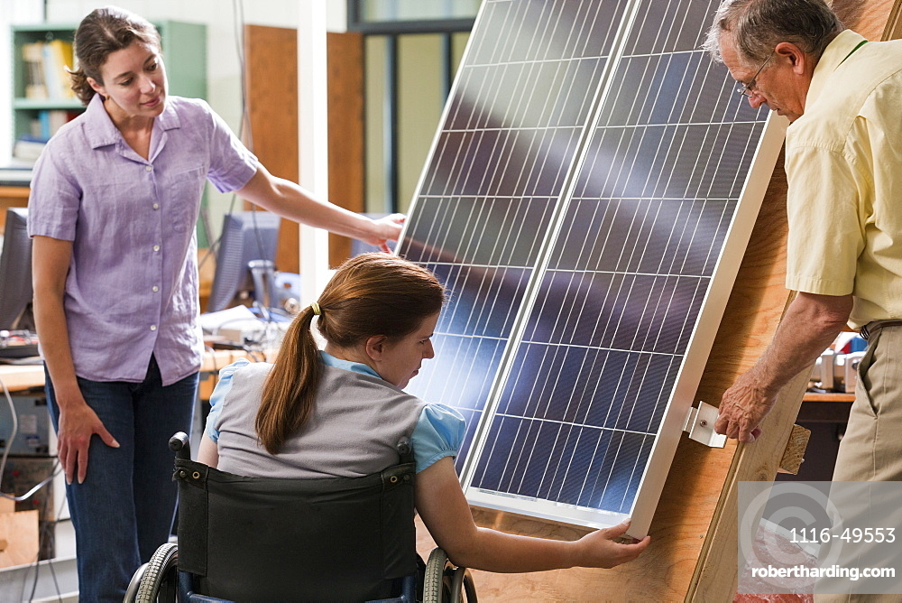 Professor explaining mounting of photovoltaic module to engineering students