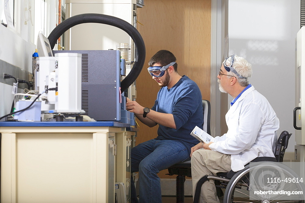 Professor with muscular dystrophy and engineering student using the thermogravimetric analyzer in a laboratory