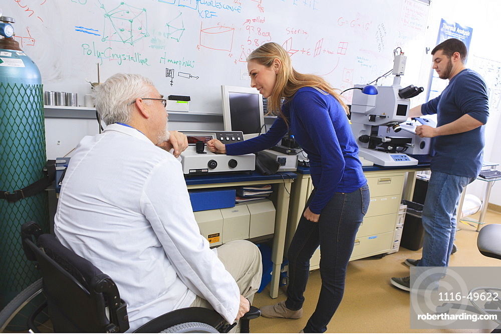 Professor with muscular dystrophy advising engineering students in chemistry laboratory working on x-ray fluorescence analyzers