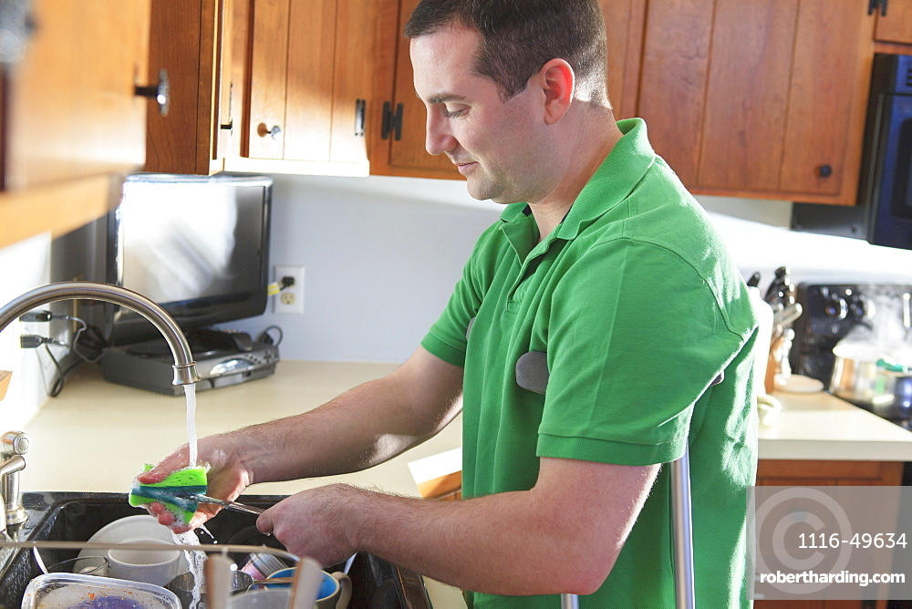 Man after anterior cruciate ligament (ACL) surgery with crutches washing dishes in the kitchen