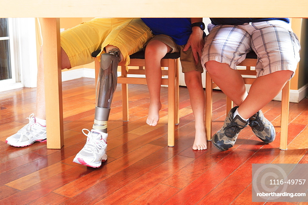 Grandmother with a prosthetic leg at a table with her grandchildren