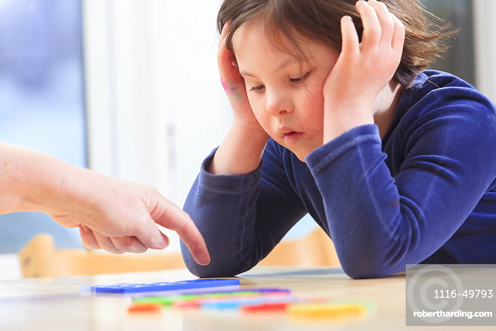 Little girl with Down Syndrome playing a learning game with her Mom