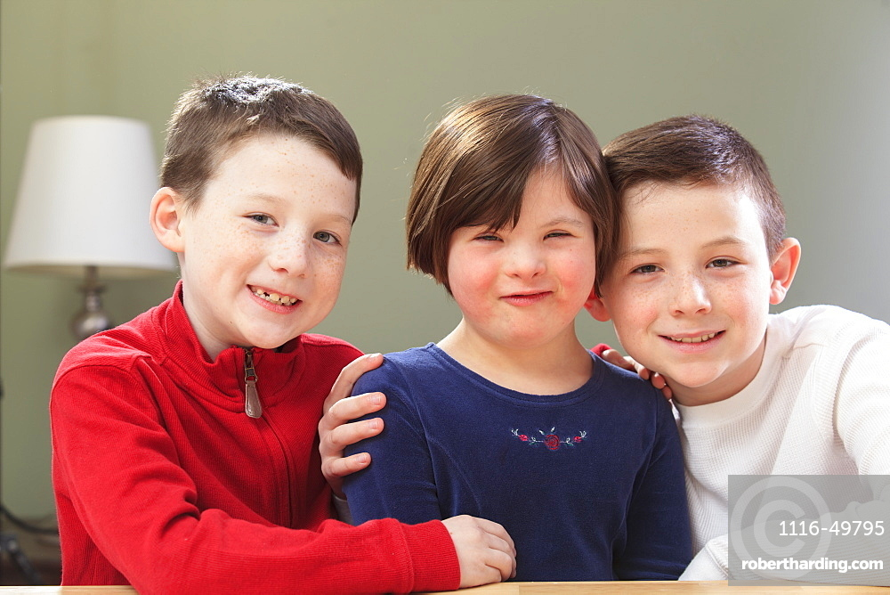 Little girl with Down Syndrome playing with her brothers