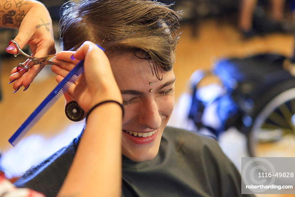 Trendy man with a spinal cord injury at a hair salon getting a hair cut