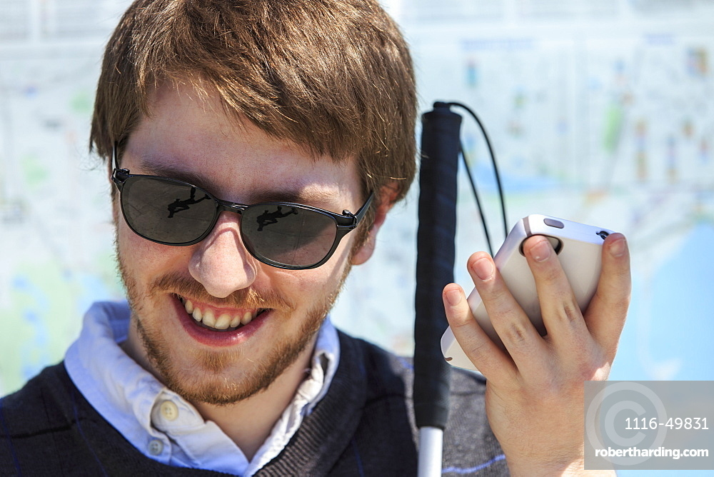 Young blind man with cane using assistive technology