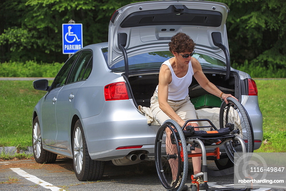 Woman with Spinal Cord Injury taking her wheelchair out of her car