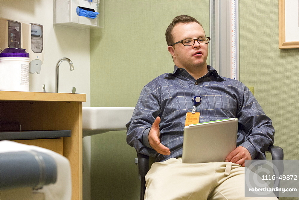 Hospital aid worker with Down Syndrome using a tablet in office