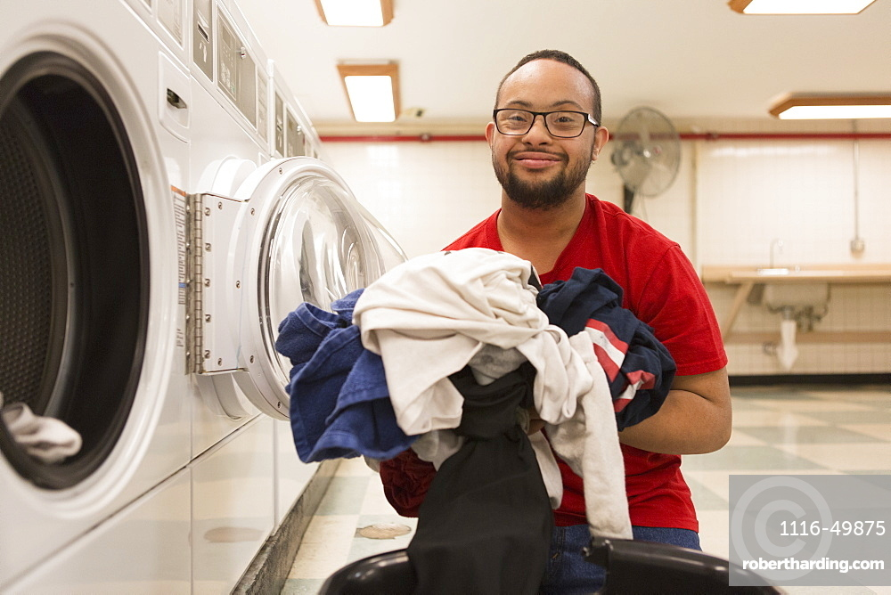 Happy African American man with Down Syndrome doing laundry in utility room