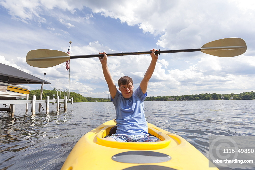 Happy young man with Down Syndrome using a kayak in a lake