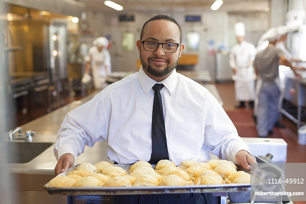 African American man with Down Syndrome as a chef holding a tray of cookies in commercial kitchen