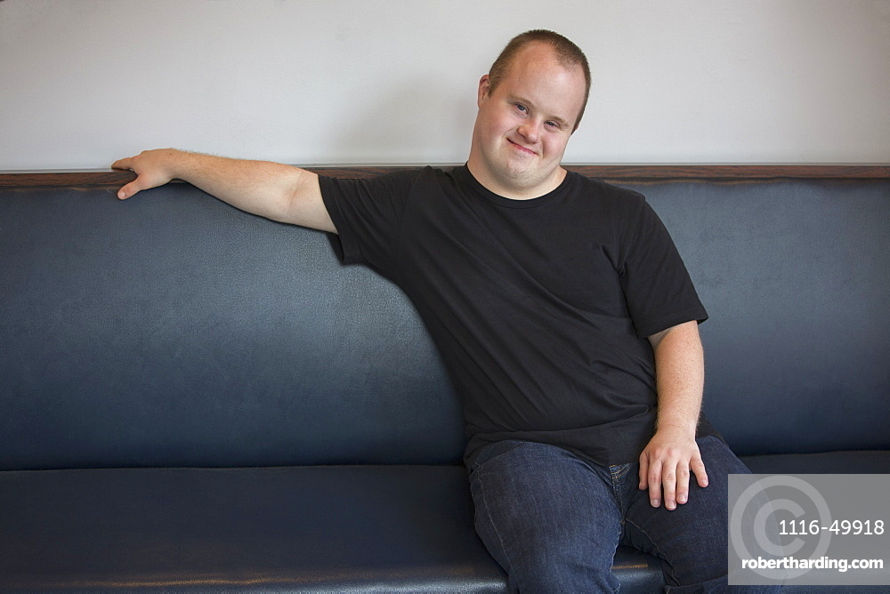 Portrait of happy waiter with Down Syndrome sitting on sofa in a restaurant