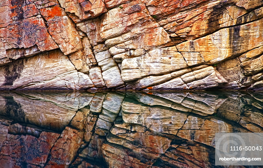 Rock wall surface reflected in tranquil water of Horseshoe Lake, Jasper National Park; Alberta, Canada