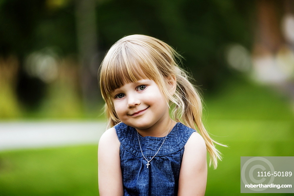 Portrait of a cute young girl with blond hair in pigtails and wearing a necklace with a cross pendant; Edmonton, Alberta, Canada
