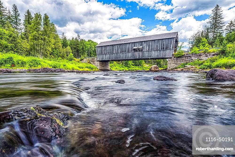 Historic covered bridge over a shallow stream; Saint John, New Brunswick, Canada