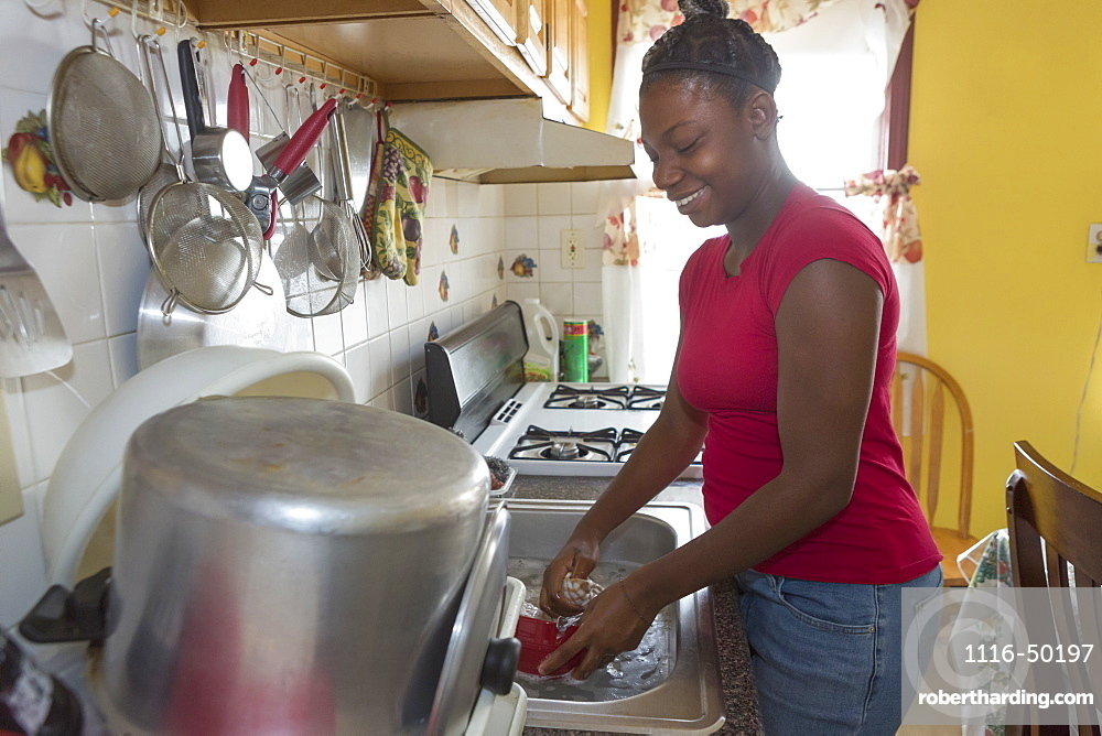 Teen suffering from Bipolar Disorder washing dishes