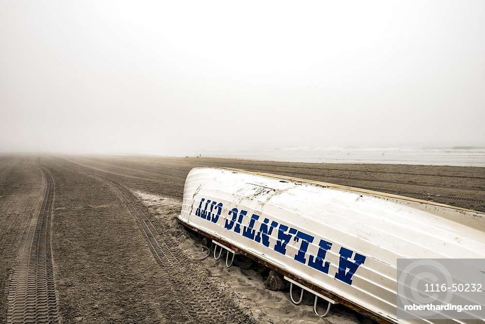 Foggy conditions on Atlantic City beach with an overturned boat on the sand; Atlantic City, New Jersey, United States of America
