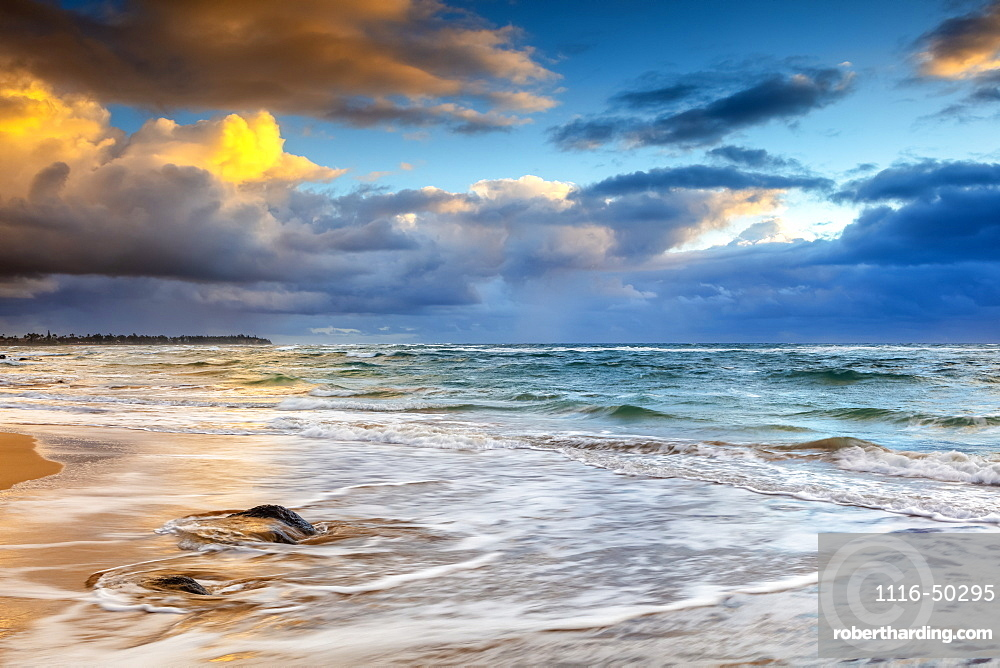 Sunrise over the Pacific Ocean from the shore of Kauai and dark clouds over the horizon; Kauai, Hawaii, United States of America