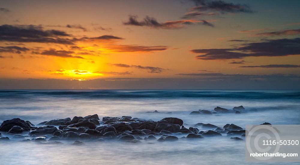 Sunrise over the Pacific Ocean from the rocks on the shore of Kauai; Kauai, Hawaii, United States of America