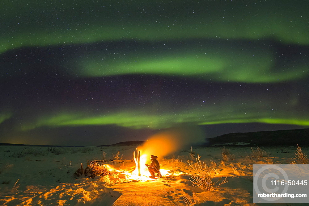 Staying warm beside a campfire on the Delta River while watching the aurora borealis on a frigid night; Alaska, United States of America