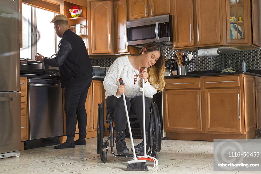 Woman with Spinal Cord Injury sweeping the floor