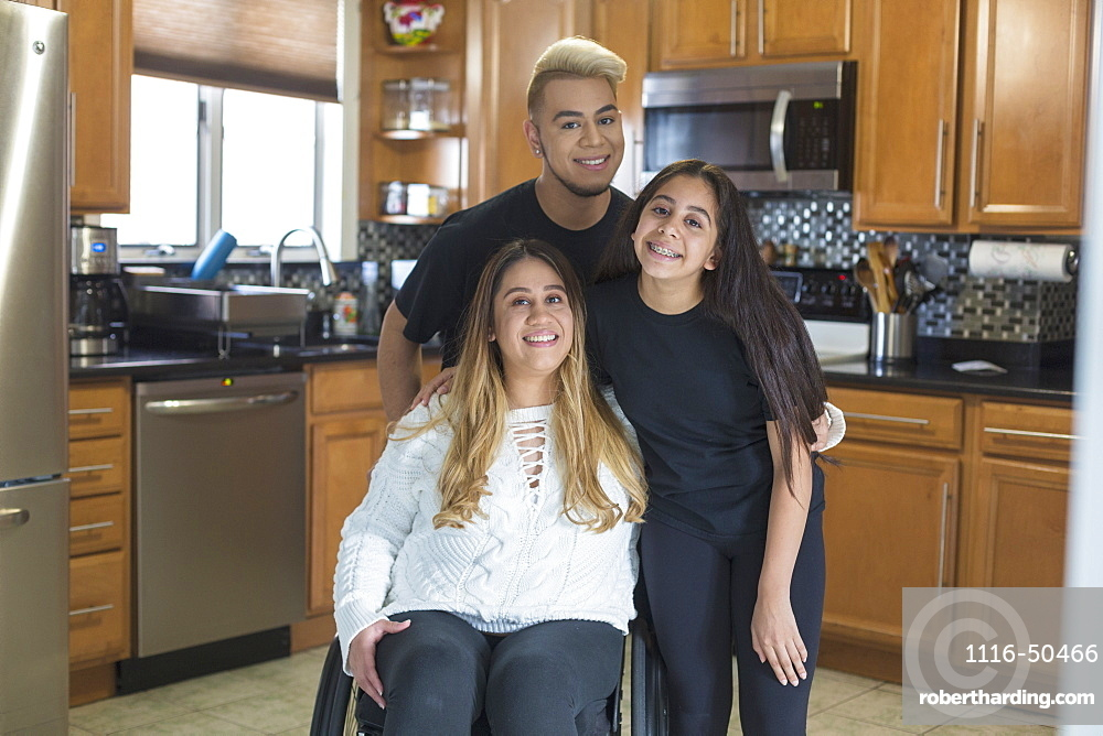 Woman who has Spinal Cord Injury standing with her friends in the kitchen