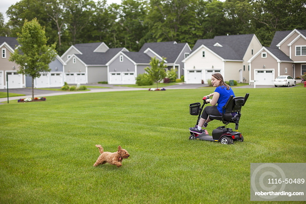 Young Woman with Cerebral Palsy riding her scooter on her lawn