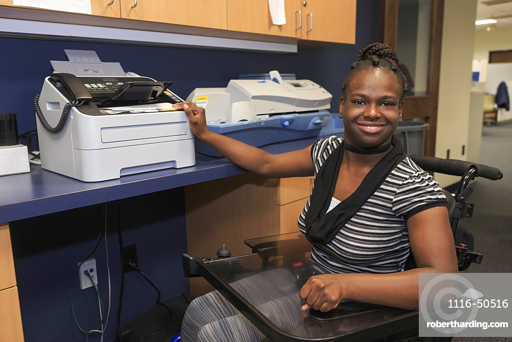 Teen with Cerebral Palsy using copier at office