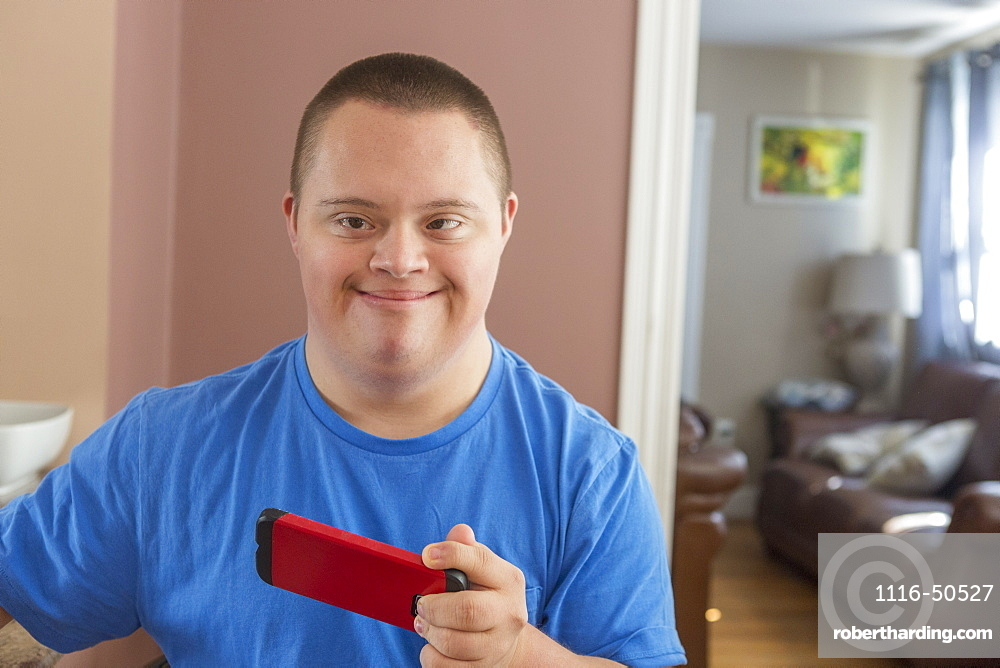 Teen with Down Syndrome holding his phone